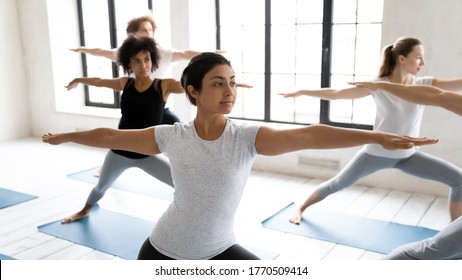 Focus on young fit indian ethnicity woman standing in virabhadrasana second position, practicing warrior II exercise with diverse motivated people at group yoga master class in modern studio.