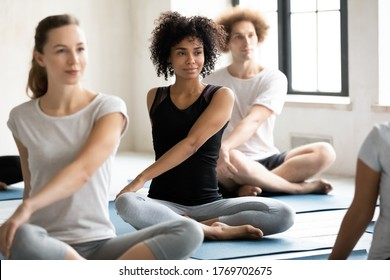 Focus on young smiling pretty african american woman enjoying morning yoga training with group of motivated healthy fit diverse people, performing parivrtta sukhasana easy twist pose indoors.