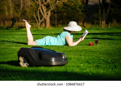 Focus on a young woman who lays on the lawn and enjoys a good book as an automatic lawn mower mows the lawn. More free time in the garden concept.