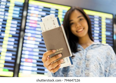 focus passport and ticket on asian hand at airport