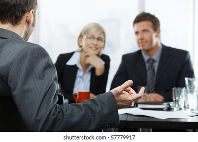 Focus placed on hand gesturing to colleagues in the background at businessmeeting.?
