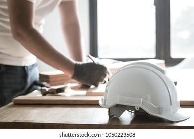 focus at safty helmet on working desk and carpenter working background