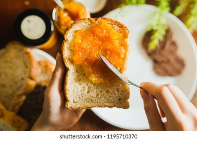 focus spreading orange marmalade jam on whole wheat bread with jam knife in hand . white dish,chocolate cookie blur are background