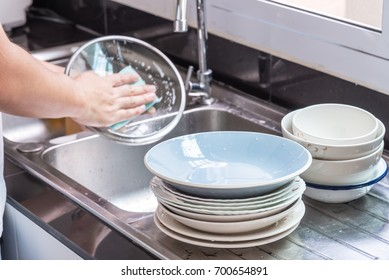 Focus at stack dish, background is stack bowl and man wash lid of pot