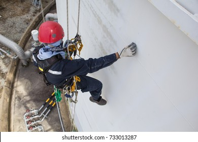 Focus Top view male worker rope access  inspection of thickness storage tank industry