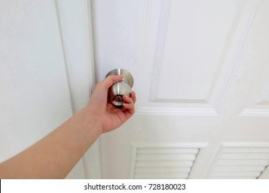 Focus Women hand going to open door knob on the white door with white wall