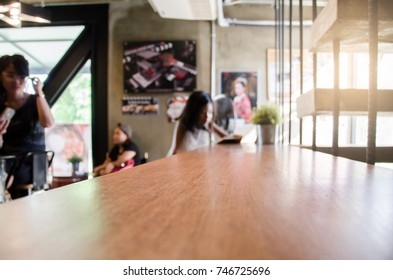 Focus wooden table. Background people in coffee shop