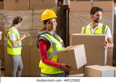 Focus of worker is holding goods and smiling to the camera in a warehouse