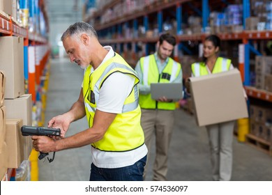 Focus of worker is working on cardboard boxes with his colleagues in a warehouse