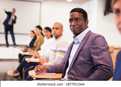 Focused African American attentively listening to lecture with colleagues at conference