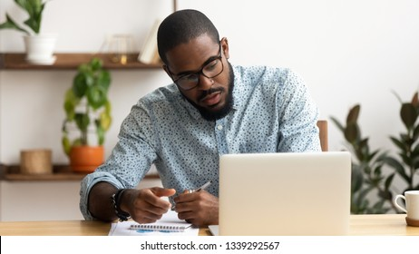 Focused African American businessman using laptop, writing notes, looking at screen, reading news, concentrated employee analyzing project results, watching webinar, distance staff training
