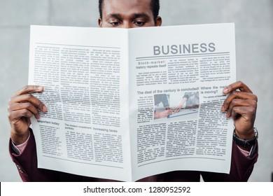 focused african american casual businessman reading newspaper