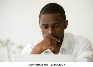 Focused african american manager working on laptop thinking hard of problem solution, concentrated black businessman concerned about work task, busy serious employee making decision online, headshot
