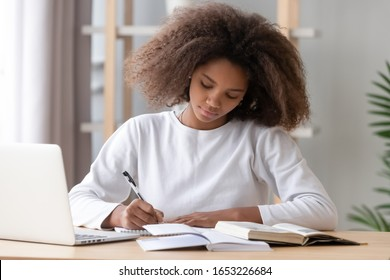 Focused african american school girl studying with books laptop preparing for test exam writing essay doing homework at home, teenage student learning assignment making notes, teen education concept