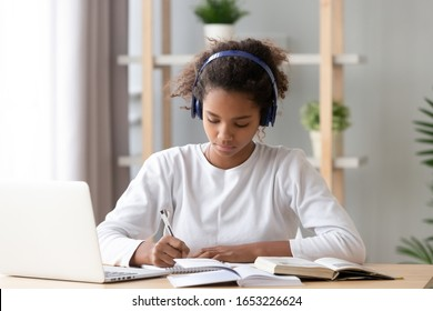 Focused african american teenage girl wearing headphones writing notes study with laptop and books, serious black female high school teen student listening audio course or music while doing homework