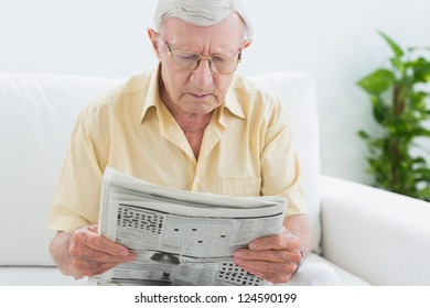 Focused aged man reading the news in the living room