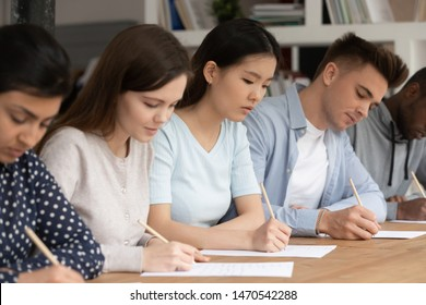 Focused asian, indian, african american and caucasian groupmates sitting at desk in classroom writing notes at lecture. Concentrated mixed race students passing evaluation examination during session.