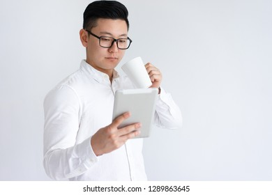 Focused Asian man using tablet and drinking coffee. Young guy standing and relaxing. Technology and break concept. Isolated front view on white background.