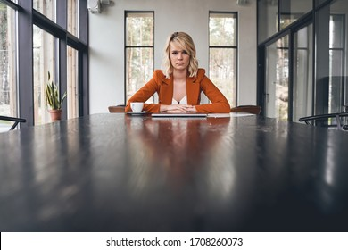 Focused attractive businesswoman with her hands clasped on the table staring in front of her