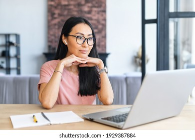 Focused beautiful asian staring on the laptop screen sitting at the desk in the modern home office, watching webinar, reading and recourching