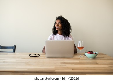 Focused black lady with curly hair browsing laptop at wooden table with glass of wine and bowl with berries at home