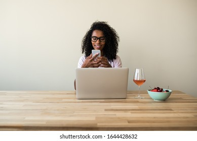 Focused black lady with curly hair browsing laptop ans using smartphone at wooden table with glass of wine and bowl with berries at home