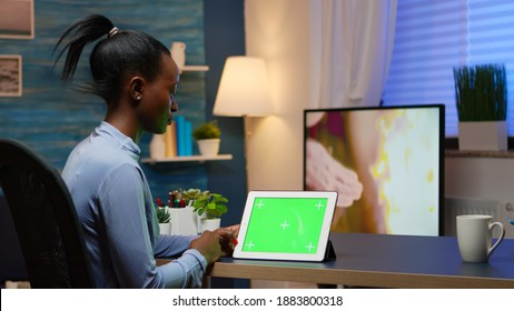 Focused black manager woman looking at tablet with green screen, studying from home using internet technology sitting in living room working overtime. Using mockup chroma key display computer.