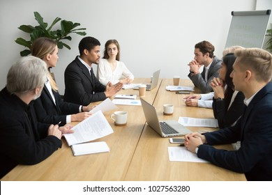 Focused black team leader talking to colleagues at meeting sitting at conference table, serious african american executive manager presenting new business idea during group briefing or negotiations