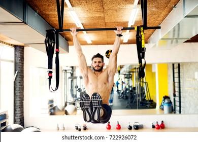 Focused bodybuilder hanging on horizontal bar performing legs raises, in the gym.
