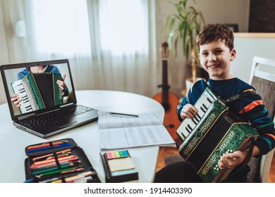 Focused boy playing accordion guitar and watching online course on laptop while practicing at home. Online training, online classes.