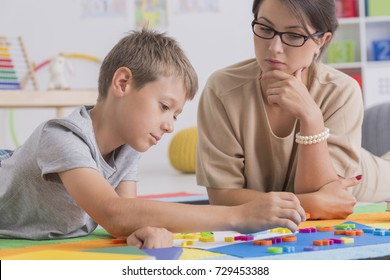 Focused boy and pretty psychotherapist during therapy in colorful classroom