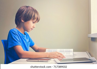 Focused boy reading a book. Tablet computer and mobile phone near to him at the table