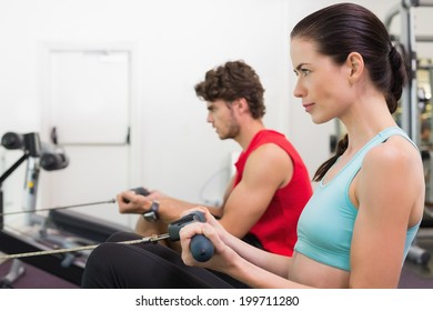 Focused brunette working out on the rowing machine at the gym