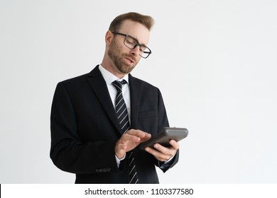 Focused business man holding and using calculator. Calculation concept. Isolated view on white background.