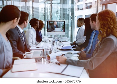Focused business people looking at screen during video conference in office