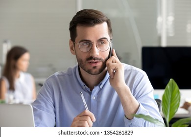 Focused businessman consulting client by phone at workplace, having conversation, making call negotiating, holding interview with aspirant, marketing manager making sell offer to customer, close up
