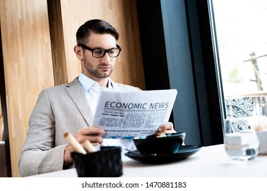 focused businessman in glasses reading newspaper in cafe