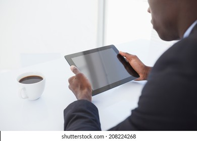 Focused businessman looking at his tablet in his office