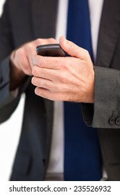 Focused businessman texting on his mobile phone on white background