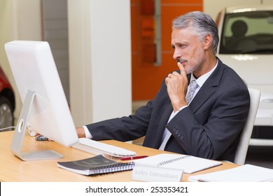Focused businessman using his laptop at new car showroom