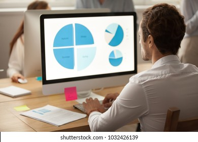Focused businessman working on statistics report using computer in coworking office, serious male marketing sales accounting manager analyzing project result data charts on monitor screen, rear view