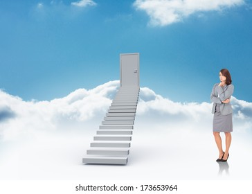 Focused businesswoman against shut door at top of stairs in the sky