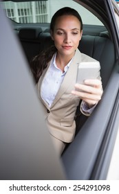 Focused businesswoman using her phone in her car