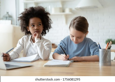 Focused busy little schoolgirls multi ethnic sisters do homework writing thinking seated at table in kitchen. Homeschooling during quarantine, self-education, gain new knowledge, brain work concept