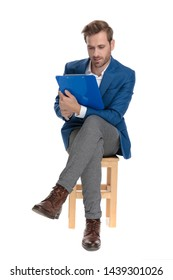 Focused casual guy reading from his clipboard while wearing an elegant suit and sitting with his legs crossed on white studio background