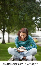 Focused casual student sitting on bench reading on campus at college