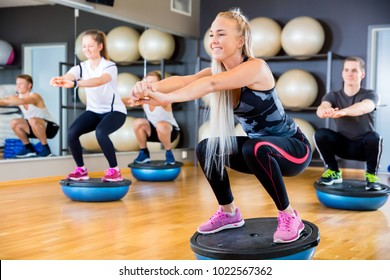 Focused and cheerful group training squats on half ball at fitness gym