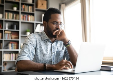 Focused concentrated young african businessman sit at desk look at laptop, serious afro american male professional analyst working online on computer data watch webinar thinking of problem solution