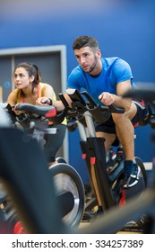Focused couple using exercise bikes at the gym