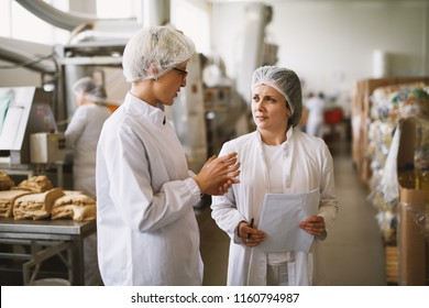 Focused dedicated female employee in sterile clothes talking about progress in food factory .